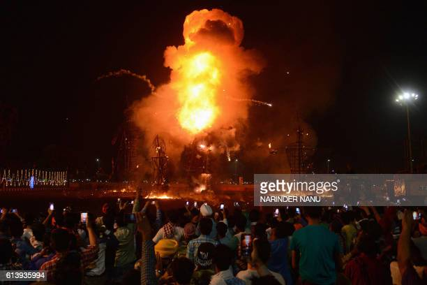 TOPSHOT Indian Hindu devotees watch an effigy of the Hindu demon king Ravana stuffed with firecrackers burn in Amritsar on October 11 2016 on the...