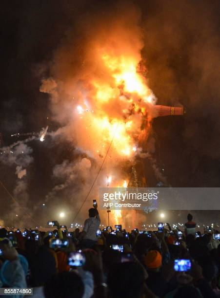 Indian Hindu devotees watch an effigy of the Hindu demon king Ravana stuffed with firecrackers burn in Amritsar on September 30 on the occasion of...