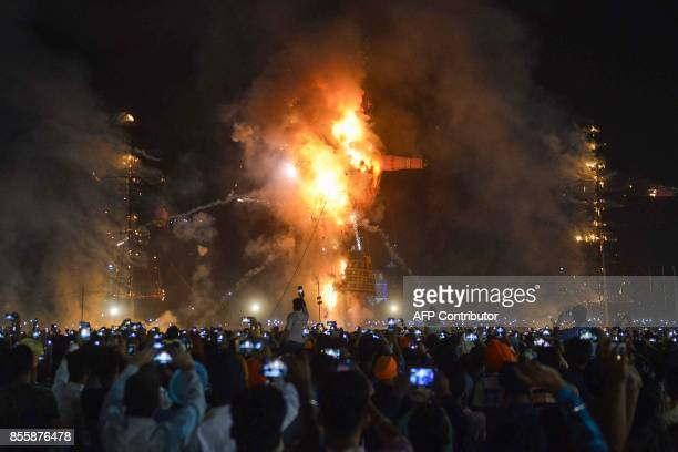TOPSHOT Indian Hindu devotees watch an effigy of the Hindu demon king Ravana stuffed with firecrackers burn in Amritsar on September 30 on the...