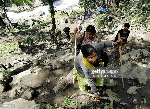 Indian Hindu female pilgrims scramble up a hill near the village of Chandanwari some 114kms south of Srinagar, 15 July 2004, during the annual...