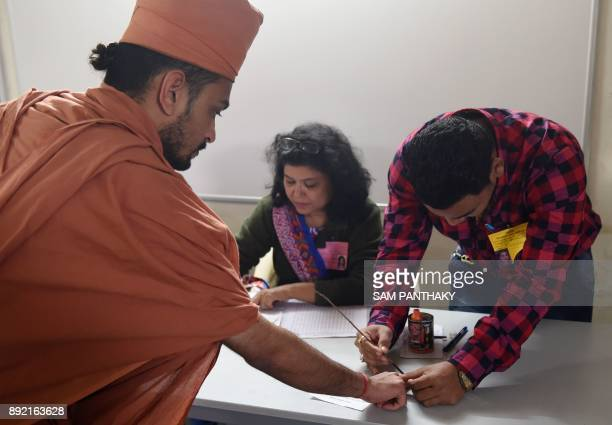 A Indian Hindu holy man from the SGVP Swaminarayan Gurukul organisation has his finger marked with ink during voting in Charodi village on December...
