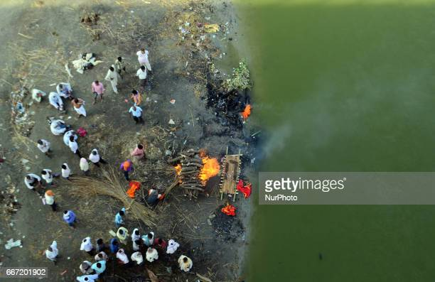 Indian hindu people gather near a dead body of their relative as they prepare to cremate on the polluted banks of Ganges river in Allahabad on April...