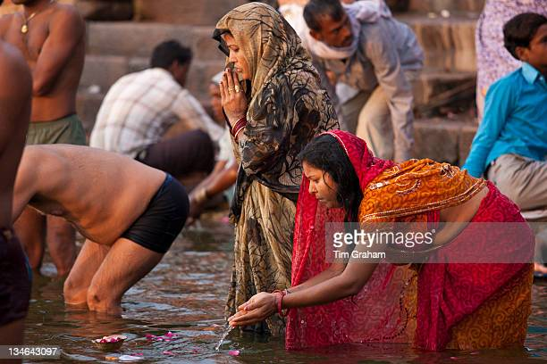Indian Hindu pilgrim bathing and praying in The Ganges River at Dashashwamedh Ghat in Holy City of Varanasi India