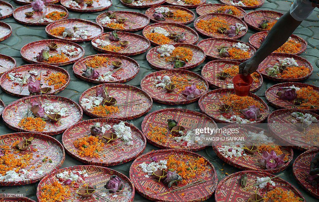 Indian Hindu pilgrims and devotees of the International Society of Krishna Conciousness (ISKON) prepare devotional trays as they wait to pull the holy rope of the Chariot of Lord Jagannath during t...