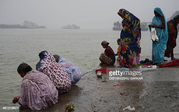 Indian Hindu pilgrims bathe in the river Ganges before leaving for the Gangasagar Mela in Kolkata on January 11 2015 Sadhus and Hindu pilgrims from...