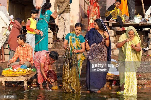 Indian Hindu pilgrims bathing in The Ganges River at Dashashwamedh Ghat in Holy City of Varanasi Benares India