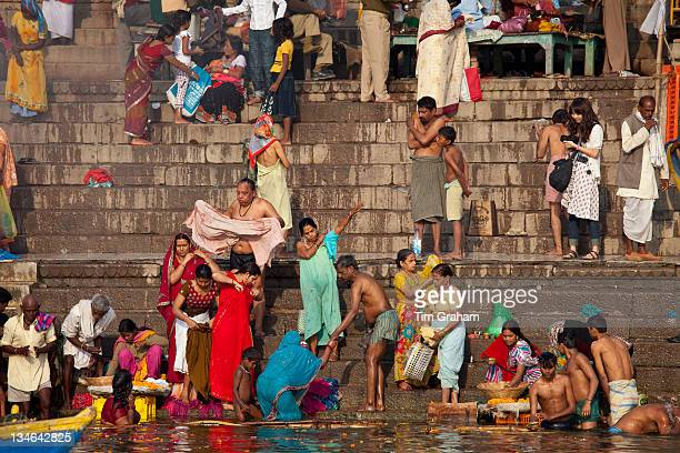 Indian Hindu pilgrims bathing in The Ganges River at Dashashwamedh Ghat in Holy City of Varanasi Benares India