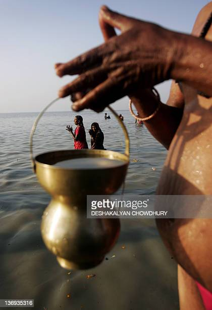 Indian Hindu pilgrims perform rituals as they worship the sun during an early morning dip at Gangasagar some 150 km south of Kolkata 14 January 2008...