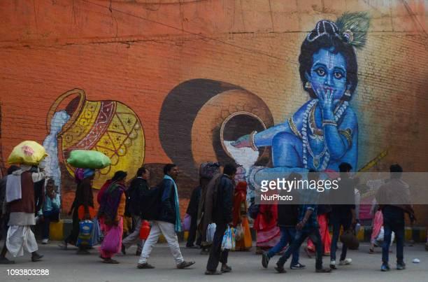Indian hindu pilgrims return after taking a holy dip at sangam, confluence of Ganges, Yamuna and mythological Saraswati rivers on the auspicious...