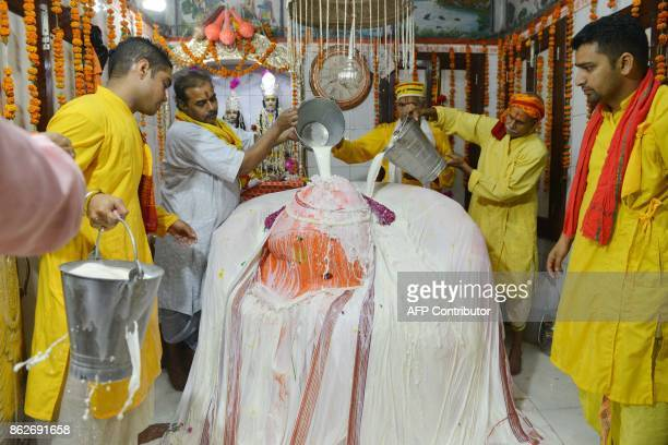 Indian Hindu priests bathe a statue of the Hindu god Hanuman with milk at the Bara Hanuman Temple in Amritsar on October 18 2017 Hindu devotees are...