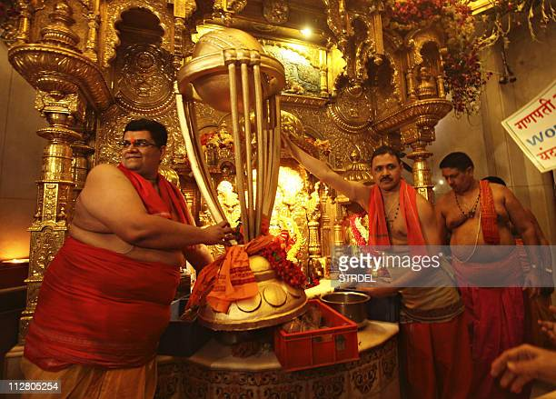 Indian Hindu priests hold a replica of the Cricket World Cup trophy during a special prayer organised to seek blessings of Hindu god Lord Ganesha for...