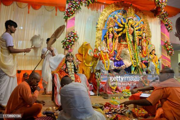 Indian Hindu priests perform a rituals in front of Srishtika Bhattacharya known as a kumari or living goddess as she is dressed as the Hindu divinity...
