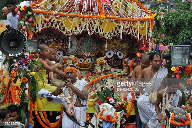 Indian Hindu priests sit on the chariot as devotees pull Lord Jagannath's chariot during Rath Yatra celebrations in Siliguri on July 10 2013 This...