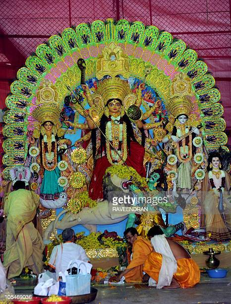 Indian Hindu priests worship in front of idols of Goddess Durga during the Durga pooja festival in New Delhi on October 15 2010 The five day worship...