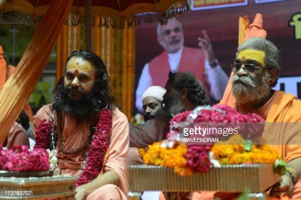 Indian Hindu sect Shankaracharya Vasudevanand Saraswati and Narendraanand Shankaracharya Saraswati look on as they sit in front of a billboard...