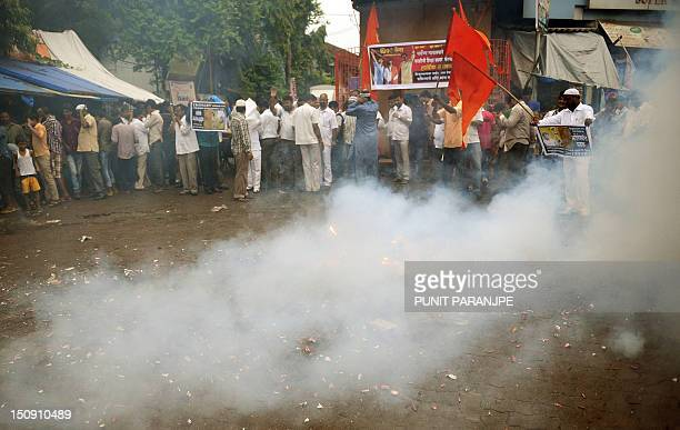 Indian Hindu Shiv Sena party activists wave flags and light fire crackers as they celebrate the Supreme Court verdict on Mohammed Kasab in Mumbai on...