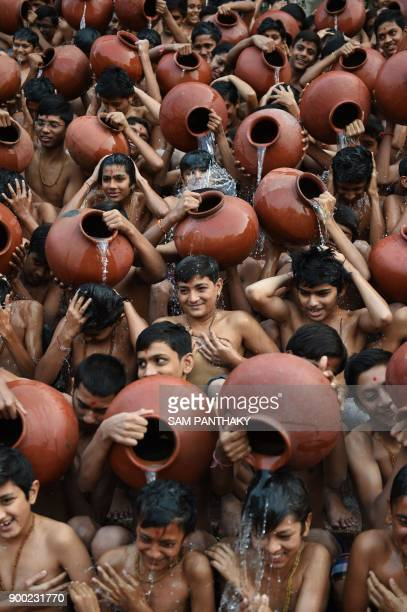 Indian Hindu students from the Swaminarayan Gurukul participate in the 'Magh Snan' or holy bath in Ahmedabad on January 1 2018 Students of...