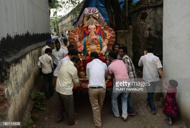 Indian Hindu take home a large idol of the elephantheaded Hindu god Lord Ganesha for Ganesh Chaturthi in Mumbai on September 9 2013 The Ganesh...