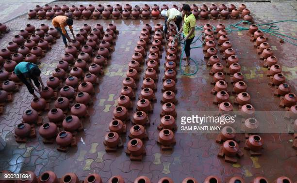 Indian Hindu volunteers fill earthen pots for students from the Swaminarayan Gurukul to participate in a 'Magh Snan' or holy bath in Ahmedabad on...