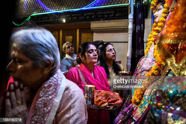 Indian Hindu wives pray as they perform rituals during the Karwa Chauth festival at a temple in New Delhi on October 27 2018 Married Hindu women...