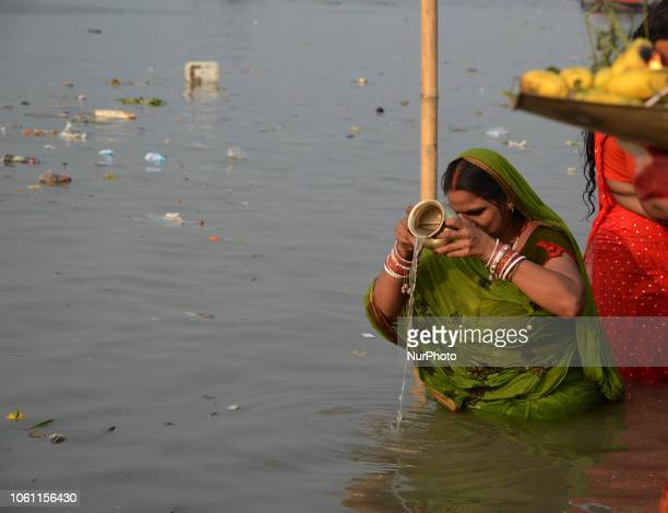 Indian Hindu woman devotee offering prayers to the Sun God on the banks of river Ganges in Kolkata India on Tuesday 13th November 2018 The Chhath...