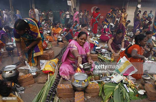 Indian Hindu woman devotees cook a traditional sweet dish on open fire during a community function on the occasion of Pongal in Dharavi on January 14...