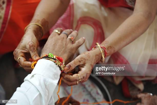 Indian hindu woman of Jain community ties 'Rakhi' on her brother's wrist during celebrations of the Raksha Bandhan or Rakhi festival in Hyderabad on...