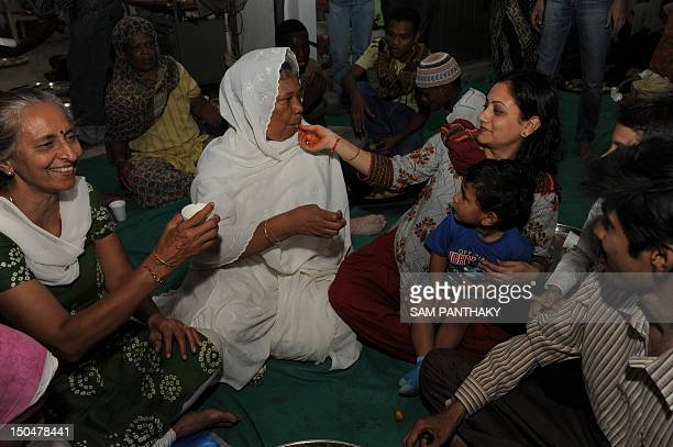 A Indian Hindu woman offers a piece of fruit to a woman of the Siddi Muslim community during Iftar on the last day of the Holy month of Ramadan in...
