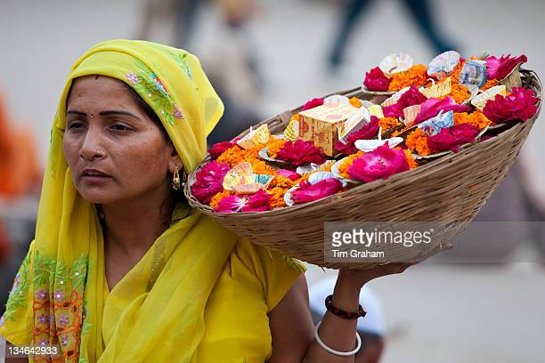 Indian Hindu woman selling ceremonial flowers and offerings during Festival of Shivaratri in holy city of Varanasi India