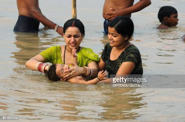 Indian Hindu women bathe a child as they take a holy dip in the river water at Sangam the confluence of the Ganges Yamuna and Saraswati rivers in...