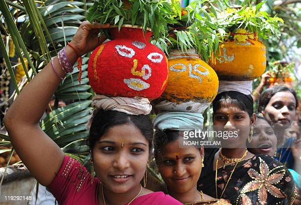 Indian Hindu women devotees carry 'ghatam' pots filled with cooked rice and decorated with neem leaves during the festival of 'Bonalu' a ritual...