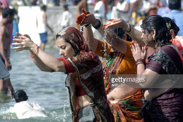 Indian Hindu women perform religious rites during ritual bathing in the River Shipra during the Kumbh Mela festival in Ujjain 05 April 2004 The month...