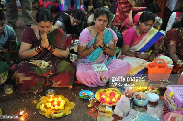 Indian Hindu women perform rituals during the prayers offer to the Hindu Goddess Lakshmi also known as 'Varalakshmi Vratham' at a temple in Hyderabad...