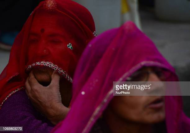 Indian hindu women wait for their bus on a table at local a bus station as they return after taking a holy dip at sangam confluence of Ganges Yamuna...