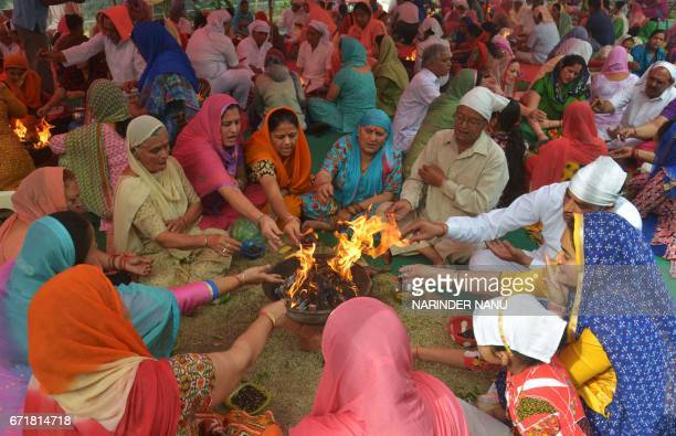 Indian Hindus devotees perform a 'Hawan' or religious ritual for world peace during a Srimad Bhagavad Gita Path event in Amritsar on April 23 2017 /...