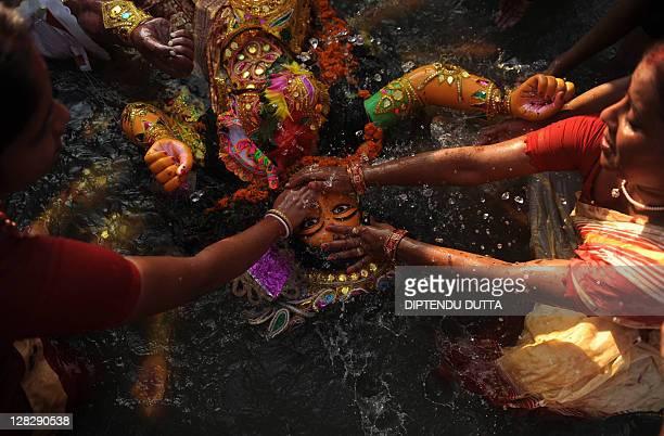 Indian Hindus immerse an idol of the goddess Durga in the river Mahananda during the Vijaya Dashami or Dusshera Festival in Siliguri on October 6 on...