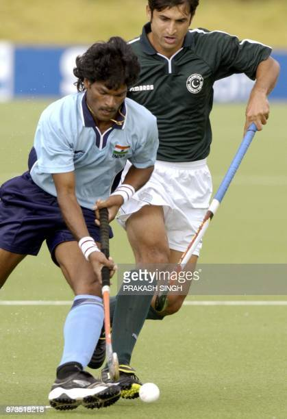 Indian hockey player Dhanraj Pillay drives the ball in front of Pakistan's Saqlain Muhammad 10 October 2002 during the semifinal match between India...