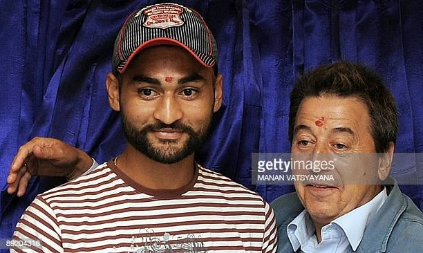 Indian hockey team captain Sandeep Singh and coach Jose Brasa pose prior to the unveiling of the new team logo in New Delhi on July 23, 2009. A...