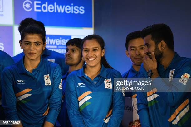 Indian hockey team captains Manpreet Singh and Rani Rampal share a light moment during the sendoff ceremony for the Indian contingent of the XXI...