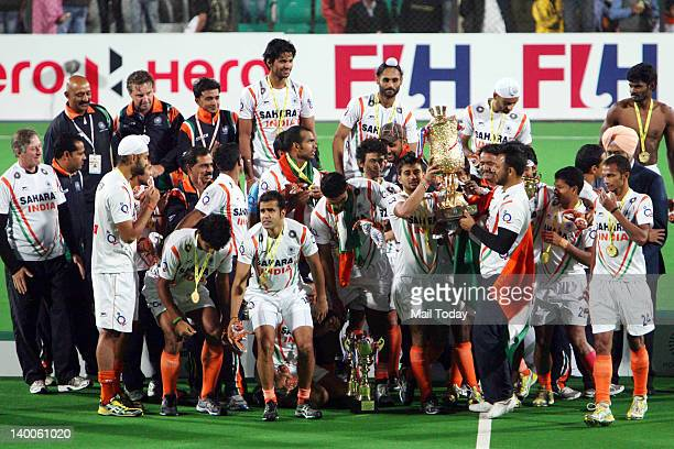 Indian hockey team poses with their trophy after winning the men field hockey match between India and France for the final position of the FIH London...