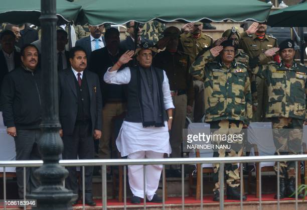 Indian Home Minister Rajnath Singh along with Indian Border Security Force officers salute as they look on the Beating Retreat ceremony near the...