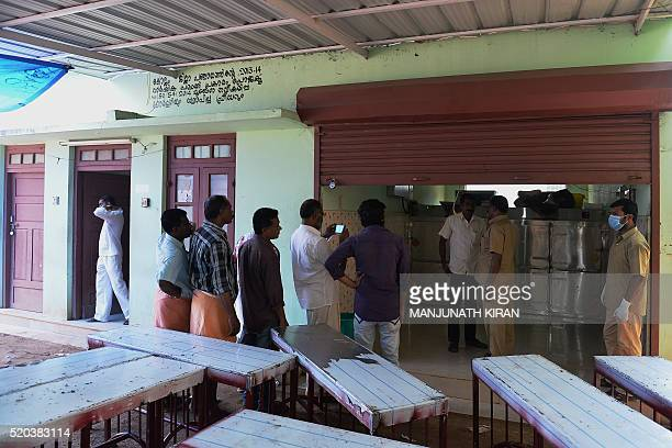 Indian hospital staff officials and relatives gather near freezers where unclaimed bodies have been kept at the mortuary of Kollam District Hospital...