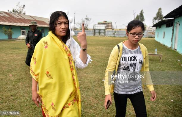 Indian human rights activist and election candidate Irom Sharmila shows her finger ink mark as she walks after casting her vote in state assembly...