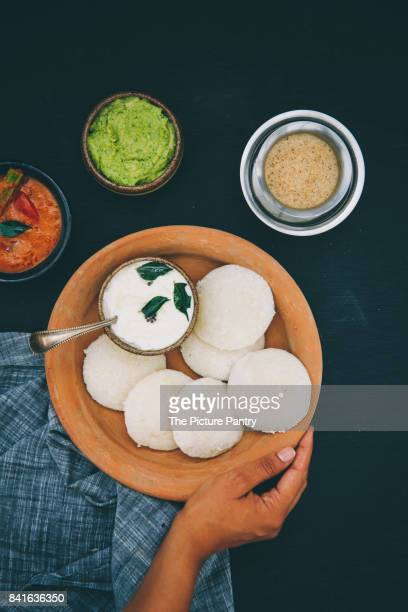 Indian idly with chutney's and filter coffee. A traditional south Indian breakfast of fresh steamed Indian Idly (Idli / rice cake) served with green coriander chutney and coconut chutney.