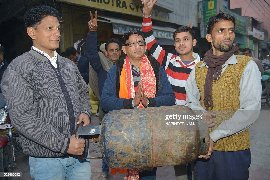 Indian independent candidate for the Punjab Legislative Assembly Bal Krishan Sharma and supporters carry a gas cylinder Sharma`s election symbol...