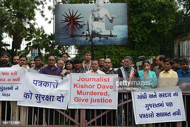 Indian journalists and supporters hold banners as they participate in a rally in support of slain journalist Kishorebhai Dave who was murdered in his...