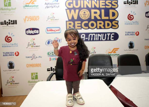 Indian Jyoti Amge the world's shortest woman according to the Guinness Book of Records poses for pictures during an event in Kuwait City on March 14...