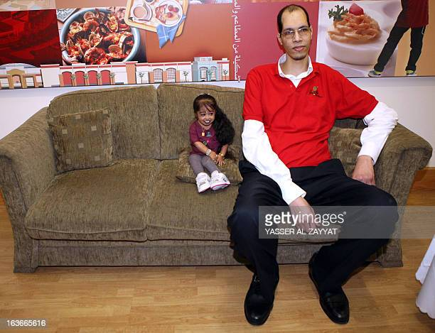 Indian Jyoti Amge the world's shortest woman sits next to Morocco's Brahim Takioullah who has the largest feet of the world according to the Guinness...