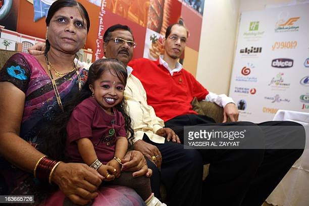Indian Jyoti Amge the world's shortest woman sits with her parents next to Morocco's Brahim Takioullah who has the largest feet in the world...