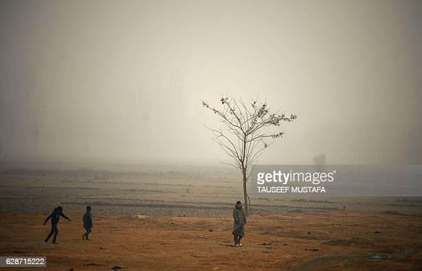 Indian Kashmiri boys walk through a field on a cold and foggy day in Srinagar on December 9 2016 / AFP / TAUSEEF MUSTAFA